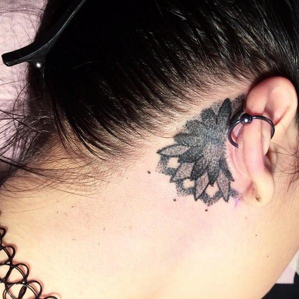 small sunflower tattoo behind ear