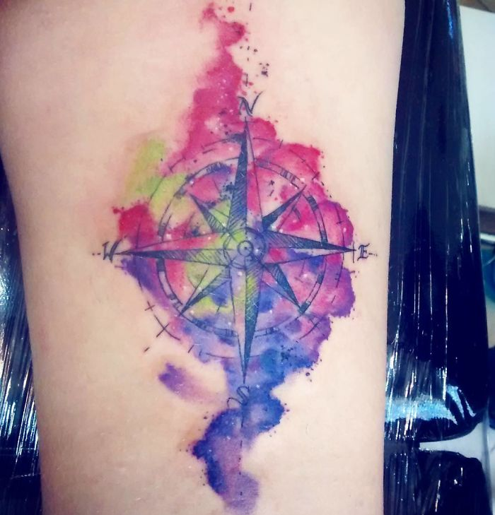 colourful compass travel tattoo on arm
