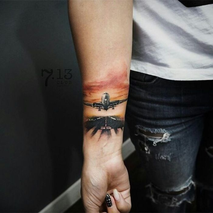 plain motivation travel tattoo on arm